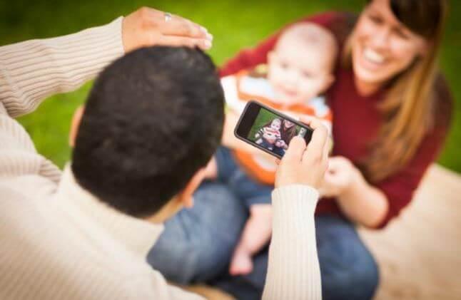 Père prenant une photo de son bébé avec le flash de l'appareil ce qui peut faire les bébés devenir aveugles