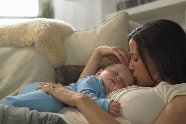 Maman embrassant son bébé endormi dans ses bras