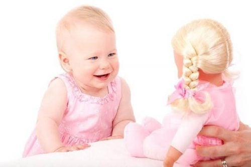 Une petite fille rie face à une poupée