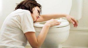 Femme au-dessus des toilettes souffrant de nausées durant la grossesse