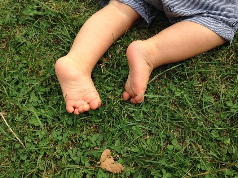 Pieds nus d'un bébé dans l'herbe