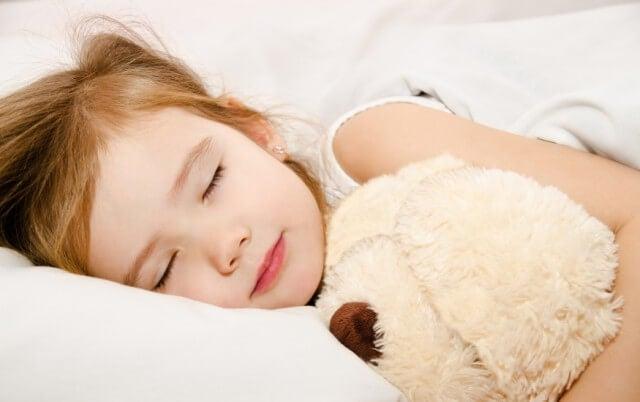 Petite fille endormie avec une peluche