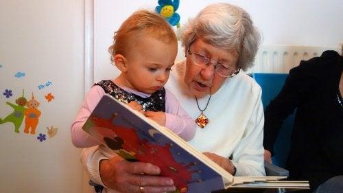 Grand-mère en train de lire une histoire à une petite fille dans ses bras