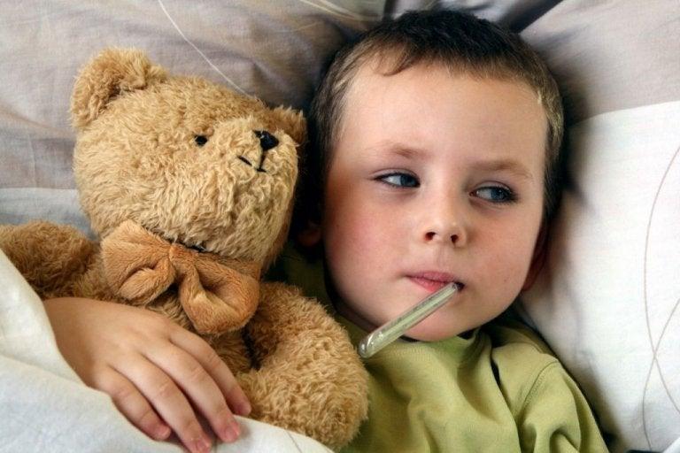 Enfant couché avec une peluche et un thermomètre dans la bouche