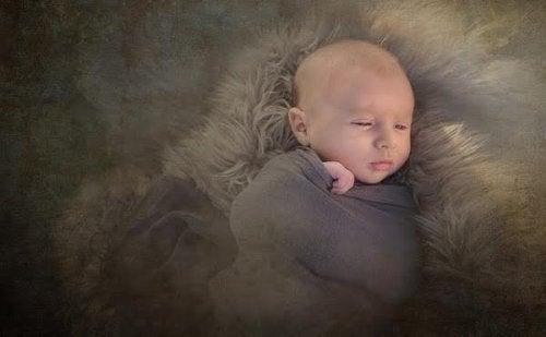 Bébé sans cheveux enveloppé dans une couverture
