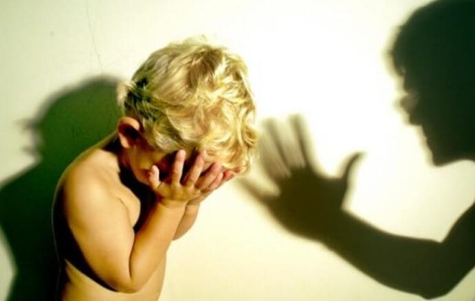 Un enfant se cache la tête dans la main face à un adulte qui le punit,