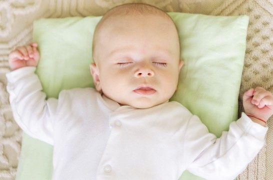 Un nouveau-né endormi sur le dos sur un coussin bien que les oreillers pour les bébés soient à éviter