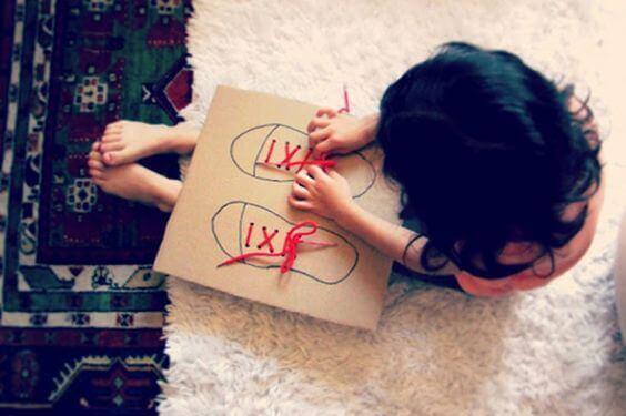 Une petite fille noue et détache les lacets de chaussures sur un jeu en carton