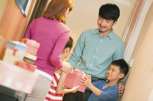 Enfant asiatique avec son père recevant chez lui une amie blanche avec sa mère
