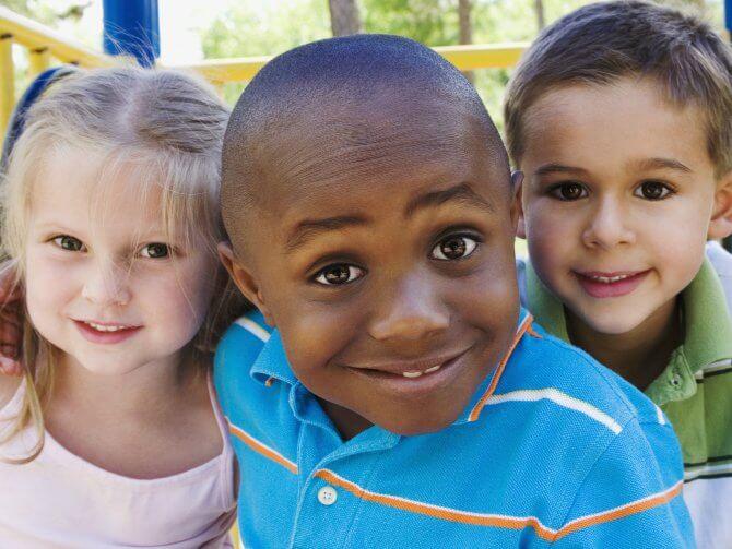 Enfant noir entouré d'enfants blancs