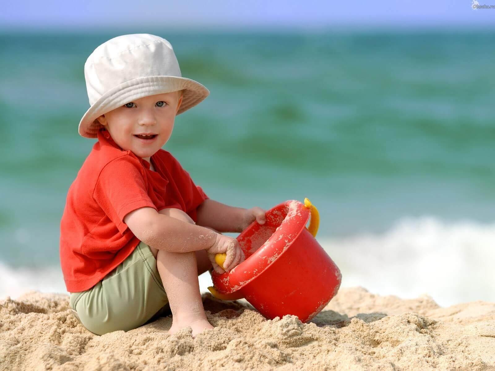 Enfant à la plage dans le sable, en plein jeu créatif avec un seau