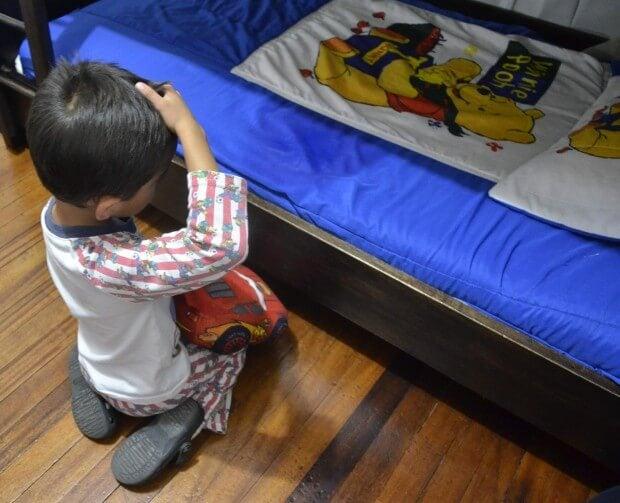 Enfant face à son lit mouillé après avoir fait pipi au lit