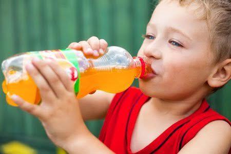 Un petit garçon en train de boire une boisson chimique, un aliment dangereux pour la santé à éviter