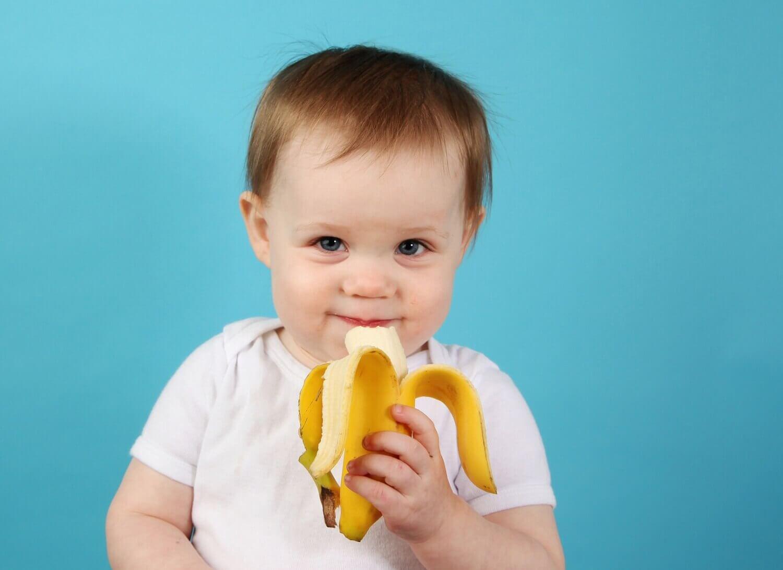 Un bébé mange une banane qui fait partie de l'alimentation complémentaire