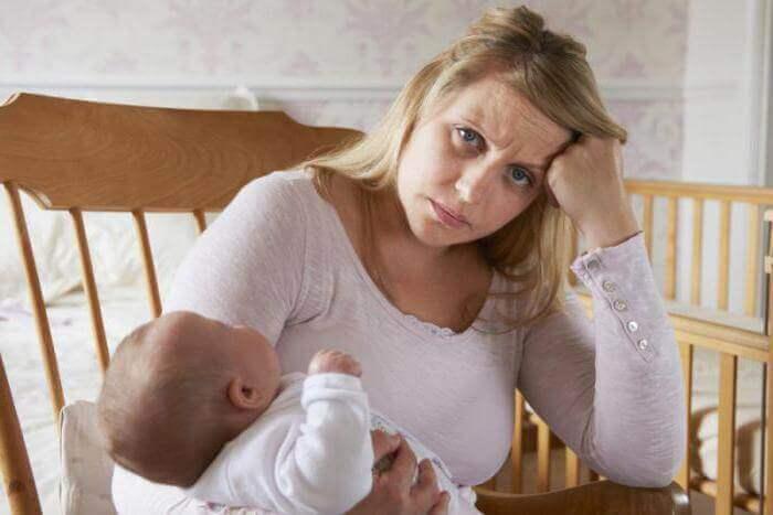 Maman contrariée avec son bébé dans ses bras qui se réveille la nuit