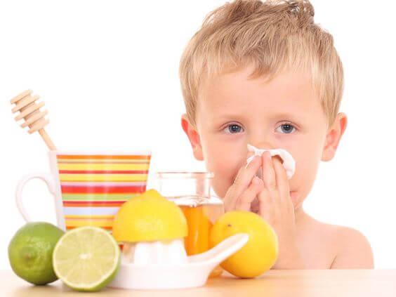 Petit garçon qui se mouche avec un thé au miel et au citron qui contribue à renforcer les défenses immunitaires des enfants