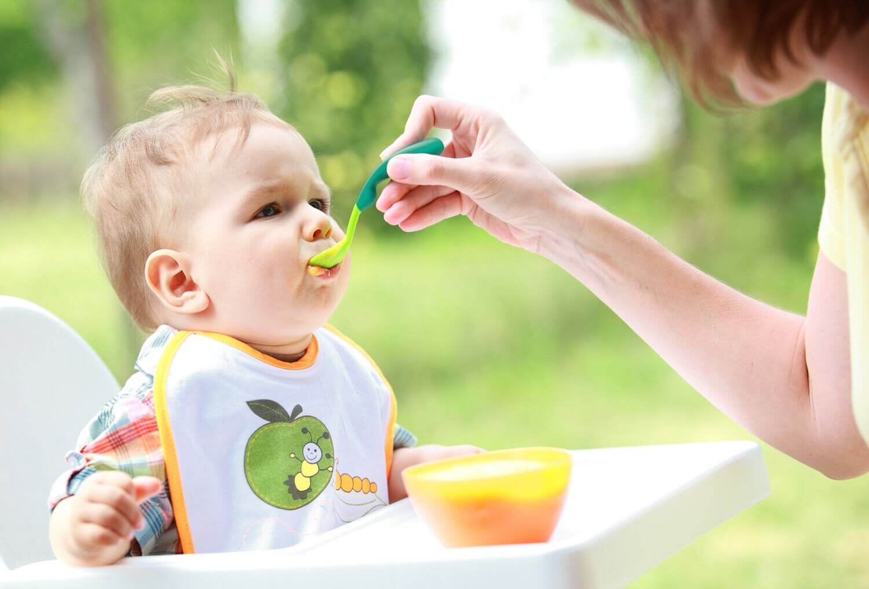 Une maman donne la cuillère à son bébé avec un bavoir