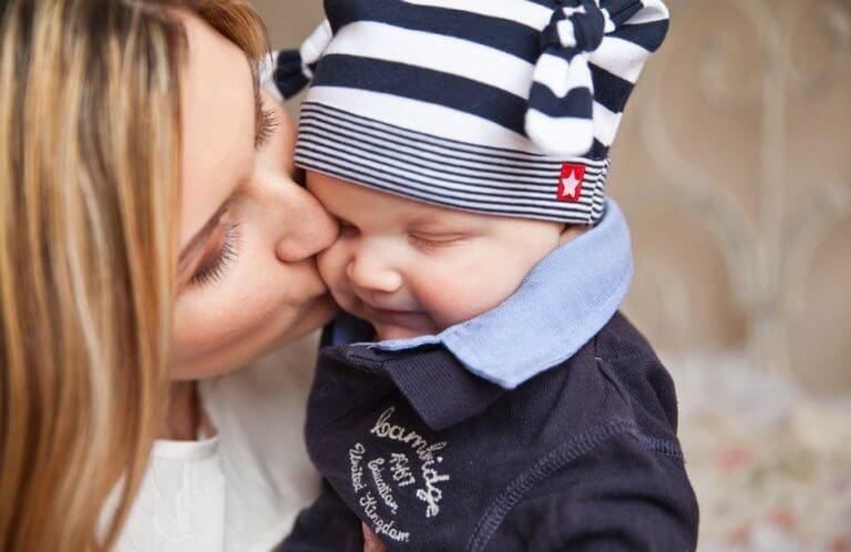 Une maman fait un bisou pour calmer les pleurs de son bébé