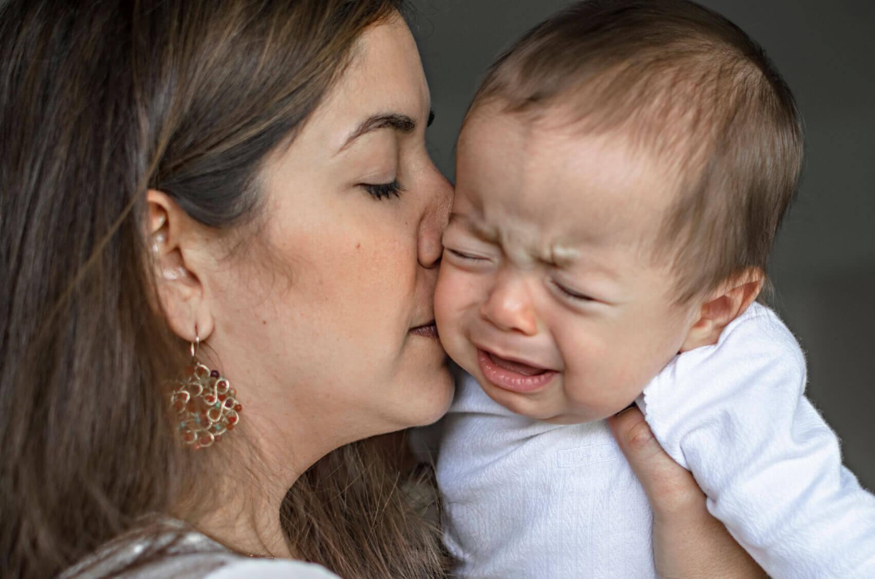 Un bébé en pleurs embrassé par sa maman