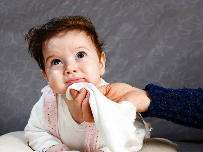 Parent essuie le menton de son bébé après des vomissements