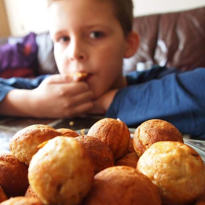 Un petit garçon mange des beignets