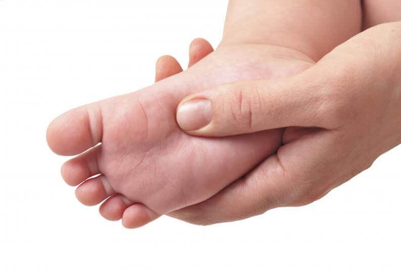 Le pied nu d'un bébé dans la main d'un adulte, une étape importante avant de choisir des chaussures pour enfants
