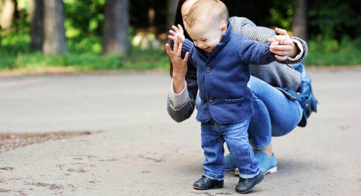 Un bébé marche avec l'aide de sa maman dans un parc