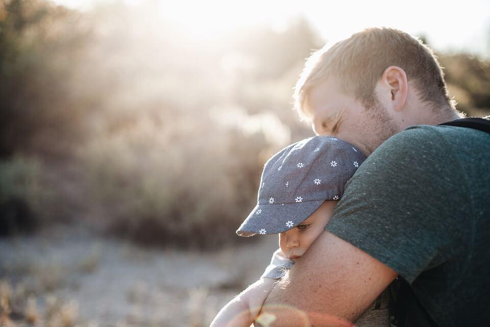 Un papa sert son bébé fort dans ses bras