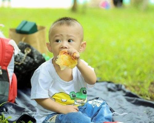 Un bébé mange dans un parc