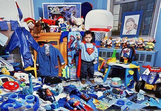 Enfant entouré de plein de jouets dans sa chambre, déguisé en Superman