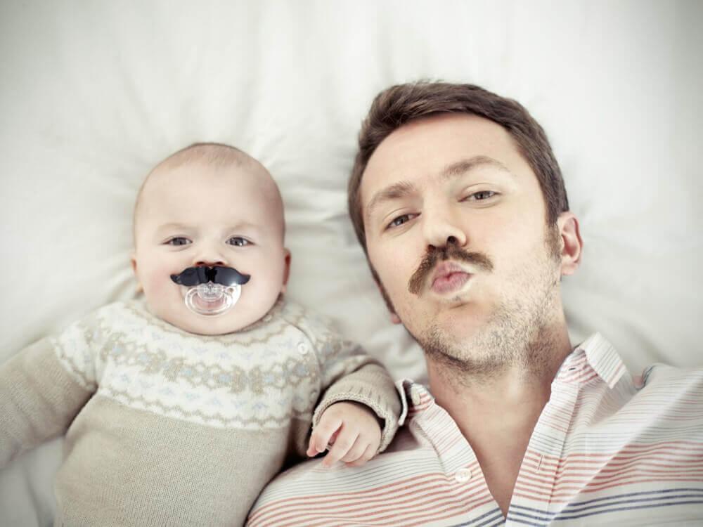 Un papa qui pose à côté de son bébé avec une fausse moustache