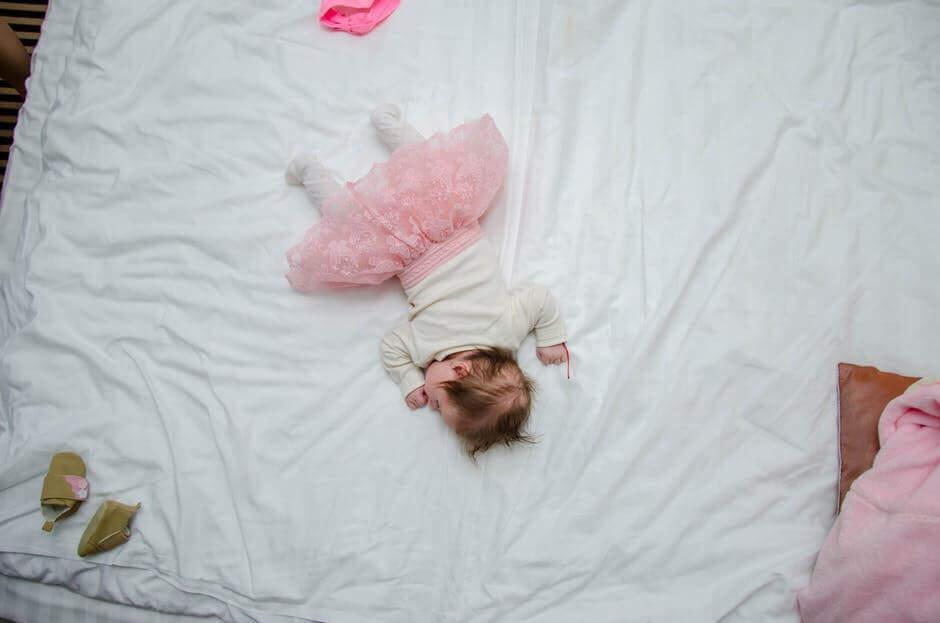 Une petit fille endormie dans un grand lit