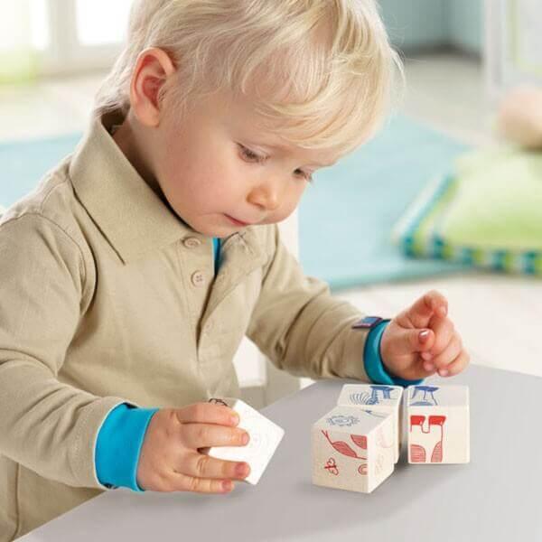 Un petit garçon de deux ans joue avec des cubes de bois