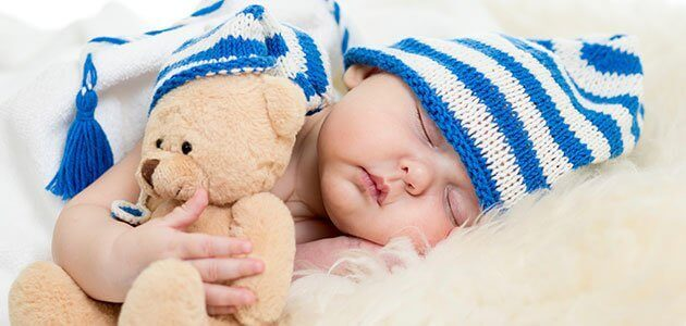 Bébé endormi avec une peluche et un bonnet sur la tête