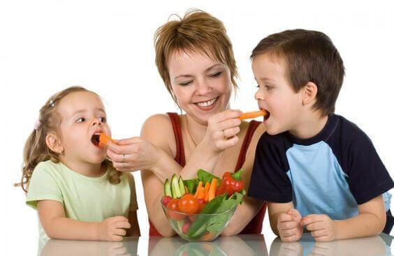 Enfants qui mangent des carottes avec leur maman