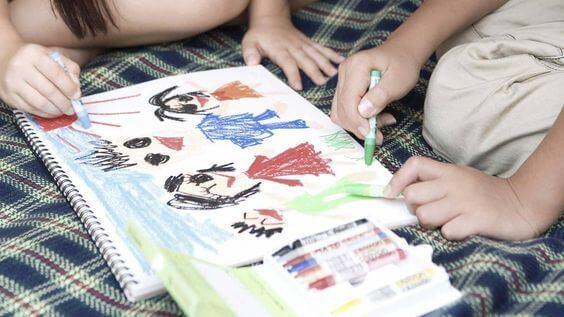 Deux enfants dessinent au crayon sur un cahier, activité qui peut stimuler la psychomotricité fine