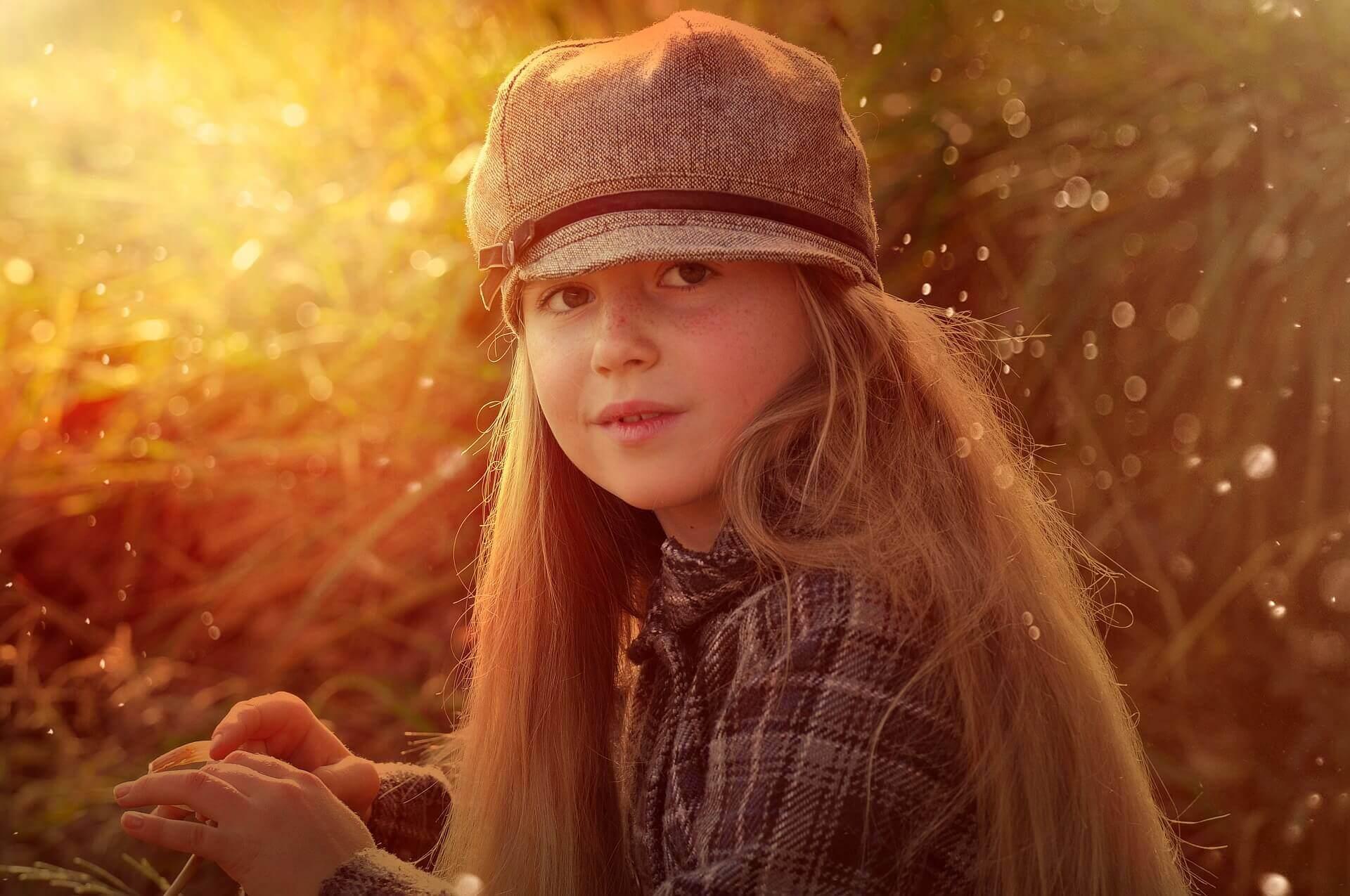 Une petite fille aux cheveux longs avec un béret