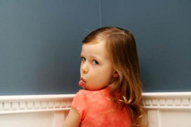 Une petite fille au coin tire la langue, un signe d'impolitesse qui peut être dû à des parents trop permissifs