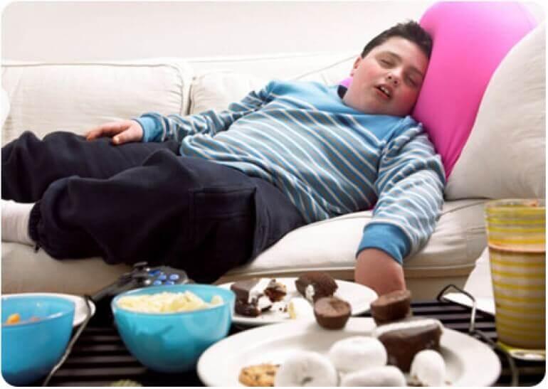 Un garcon en surpoids endormi devant des plats de chips et de gâteaux