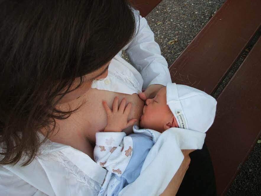 Un bébé tête le sein de sa maman, qui contient de la vitamine K