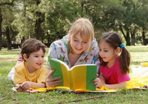 Une mère lit dans un parc un livre pour enfants à un petit garçon et une petite fille