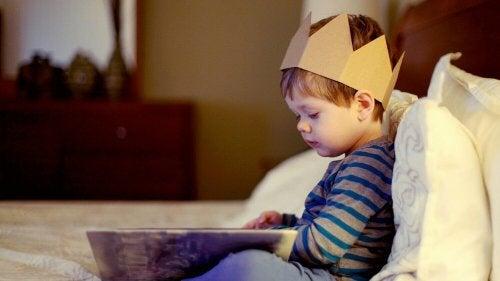 Un petit garçon en pleine lecture avec une couronne sur la tête