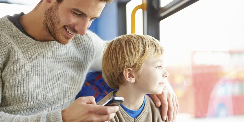 Un père sur son téléphone dans le bus avec son fils