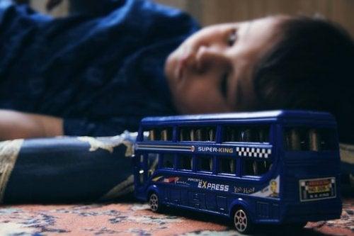 Enfant triste couché avec un jouet