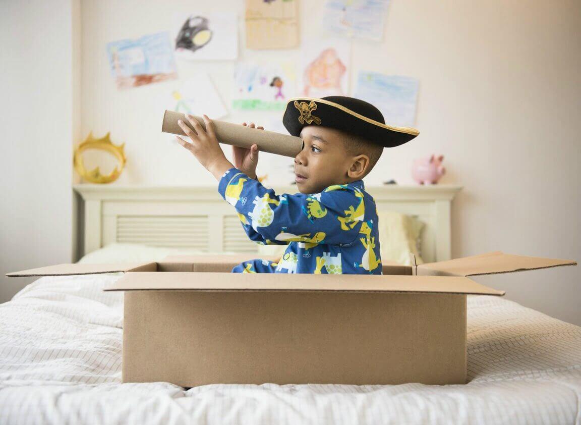 Un petit garçon qui n'a pas besoin de cadeaux et qui joue au pirate avec une boite et un tube en carton