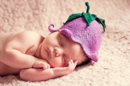 Un bébé endormi avec un bonnet de fruits sur la tête