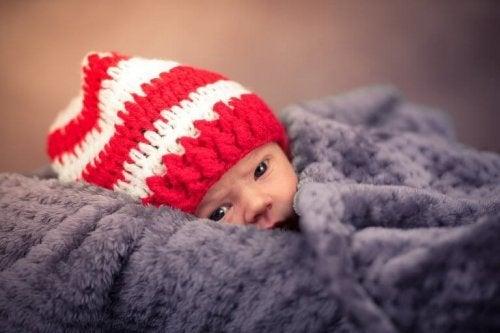 Un bébé enveloppé d'une grosse couverture avec un bonnet