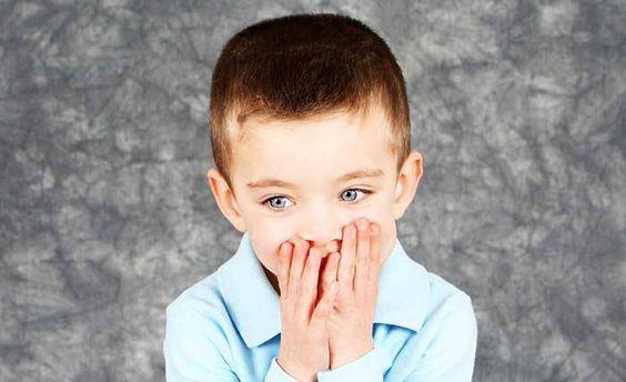 Un petit garçon avec les mains sur la bouche