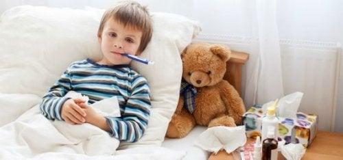 Un petit garçon malade au lit avec un thermomètre dans la bouche