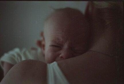 Un bébé en pleurs dans les bras de sa maman